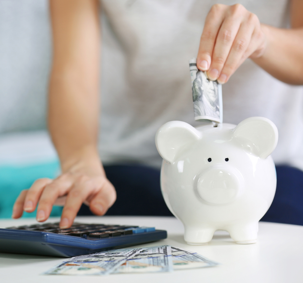 Woman putting money on piggy bank